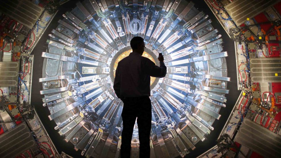 A visitor takes a phone photograph of a large back lit image of the Large Hadron Collider (LHC) at the Science Museum's 'Collider' exhibition in London, England. (Photo by Peter Macdiarmid/Getty Images)