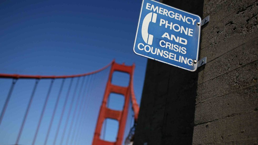 A sign for an emergency phone is seen on the span of the Golden Gate Bridge. An estimated 1,300 people are believed to have jumped to their death from the bridge since it was opened in 1937. (Photo by Justin Sullivan/Getty Images)