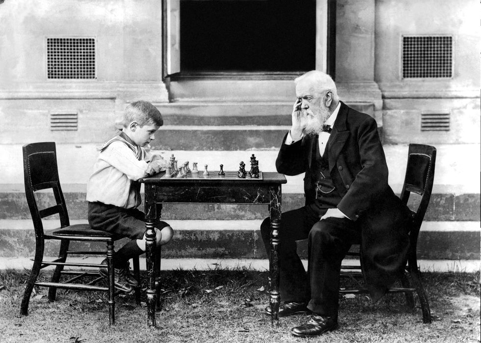 a young boy plays chess with an old man