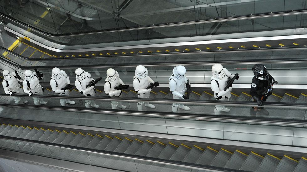 Imperial Stormtroopers and a TIE pilot (R) from the Star Wars film franchise travel up an escalator during a promotional event at the Changi International airport in Singapore.