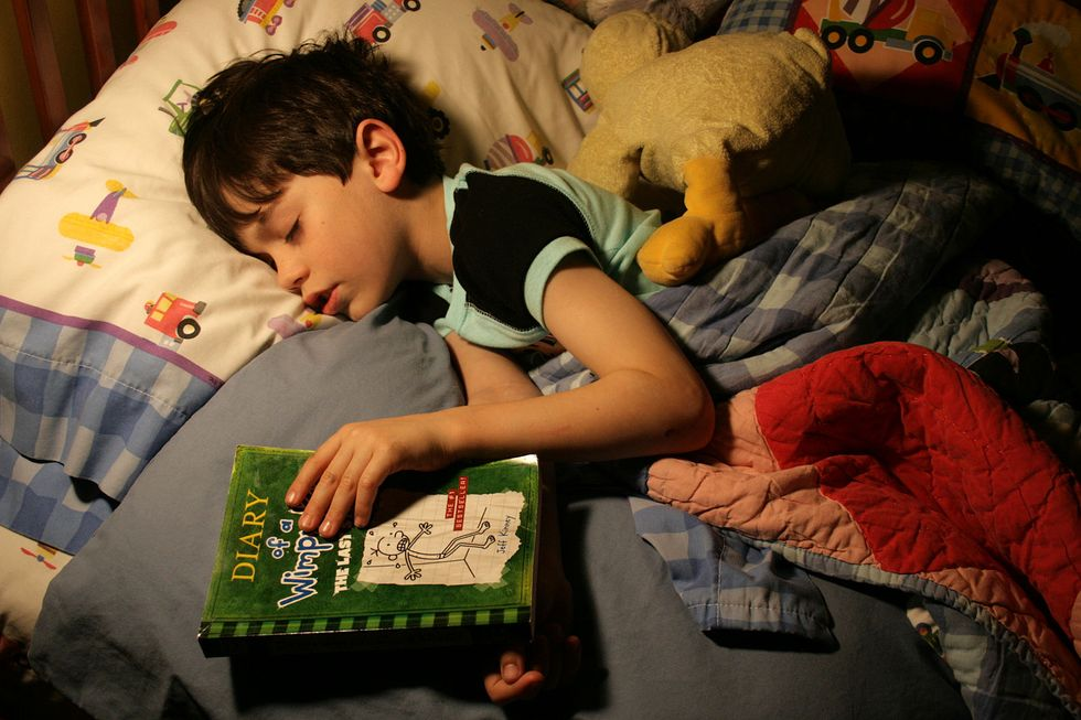 Child asleep holding book