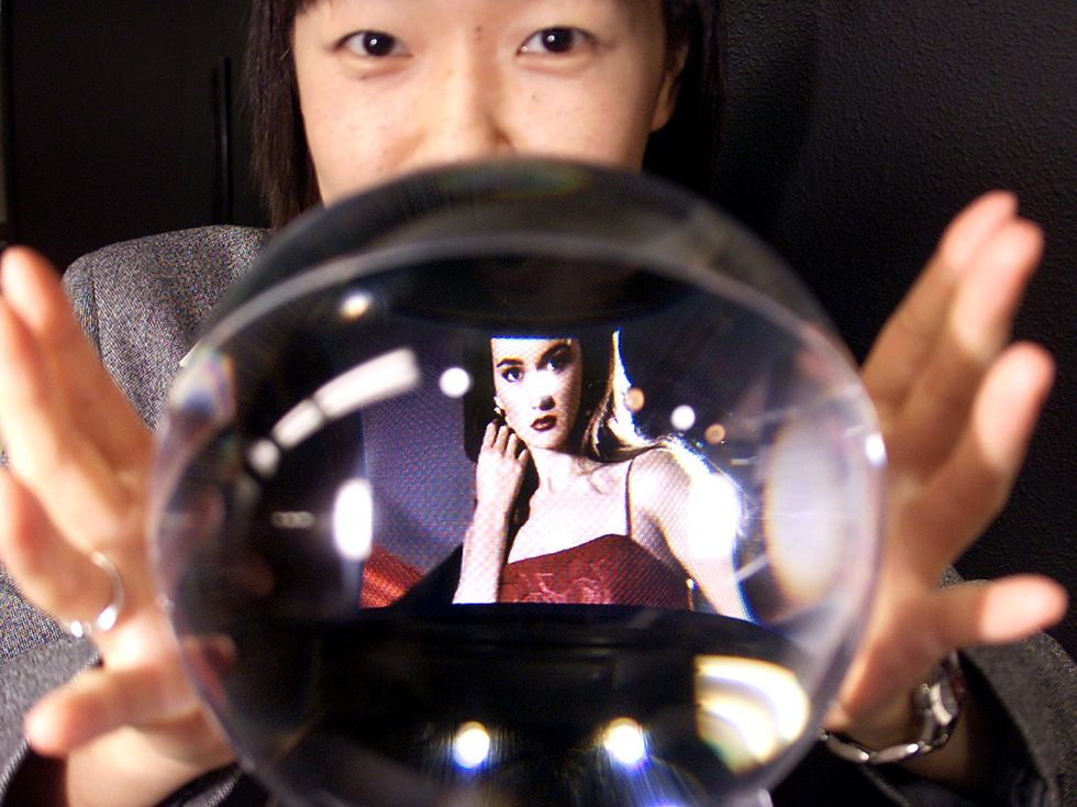 Woman with a crystal ball with an image of someone inside it.