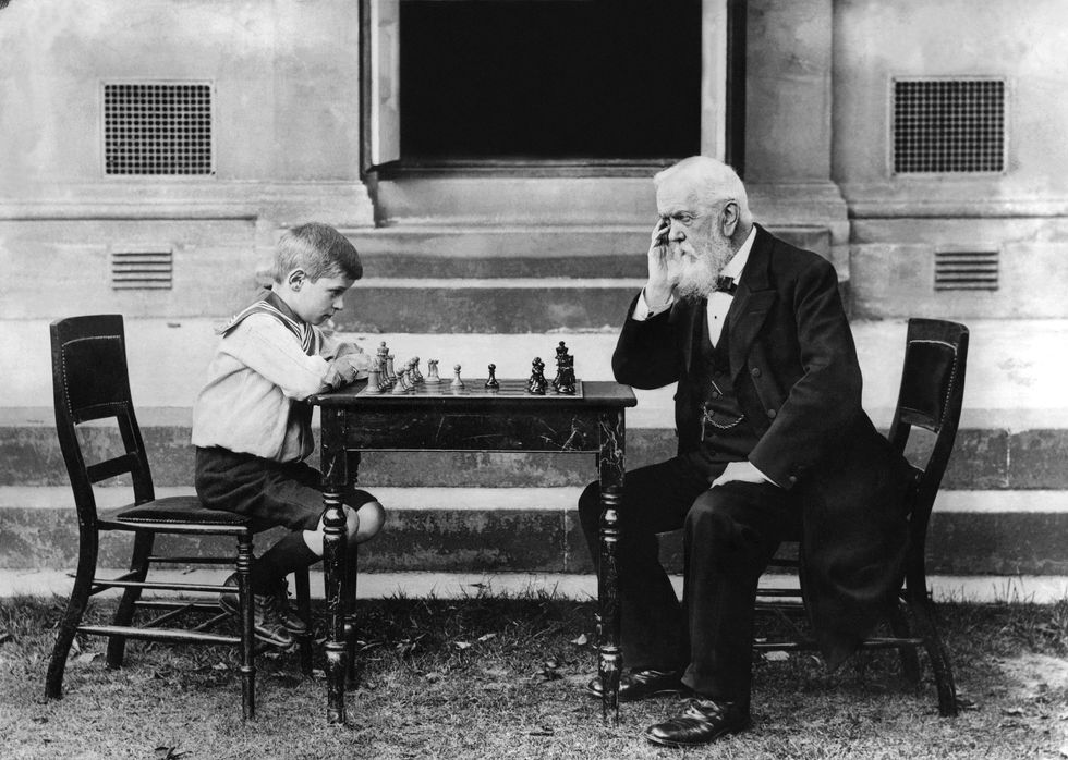 old man playing chess with a child.