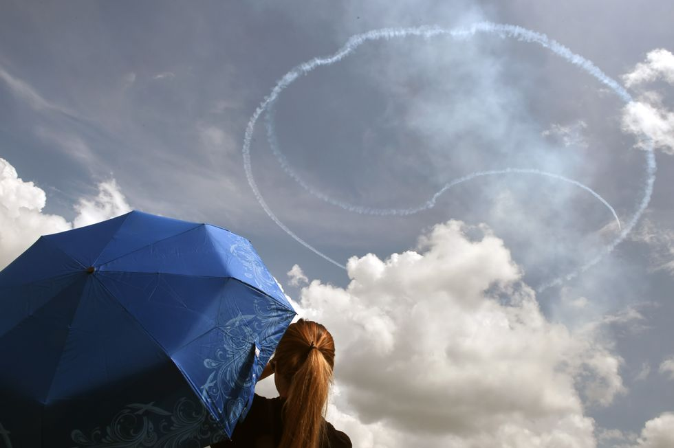 Girl with a blue umbrella sees a Yin-Yang in the sky.