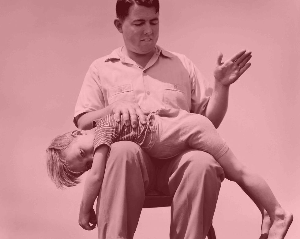 A young boy receives a spanking from his father in this staged photograph. (Kirn Vintage Stock/Corbis via Getty Images)