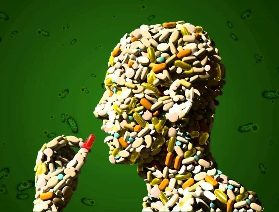 Man made of antibiotics surrounded by bacteria.