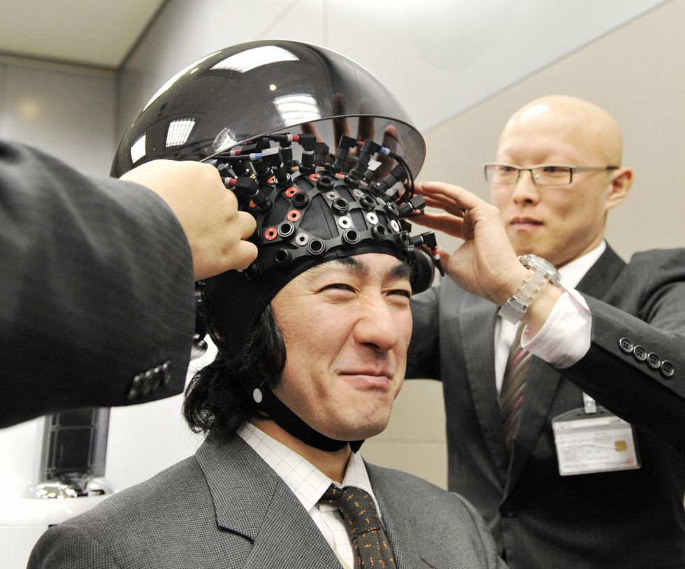 Japanese man tries out human to computer interface.