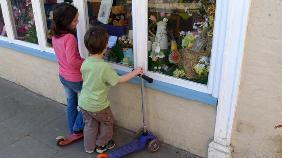 Children looking at toys through a shop window