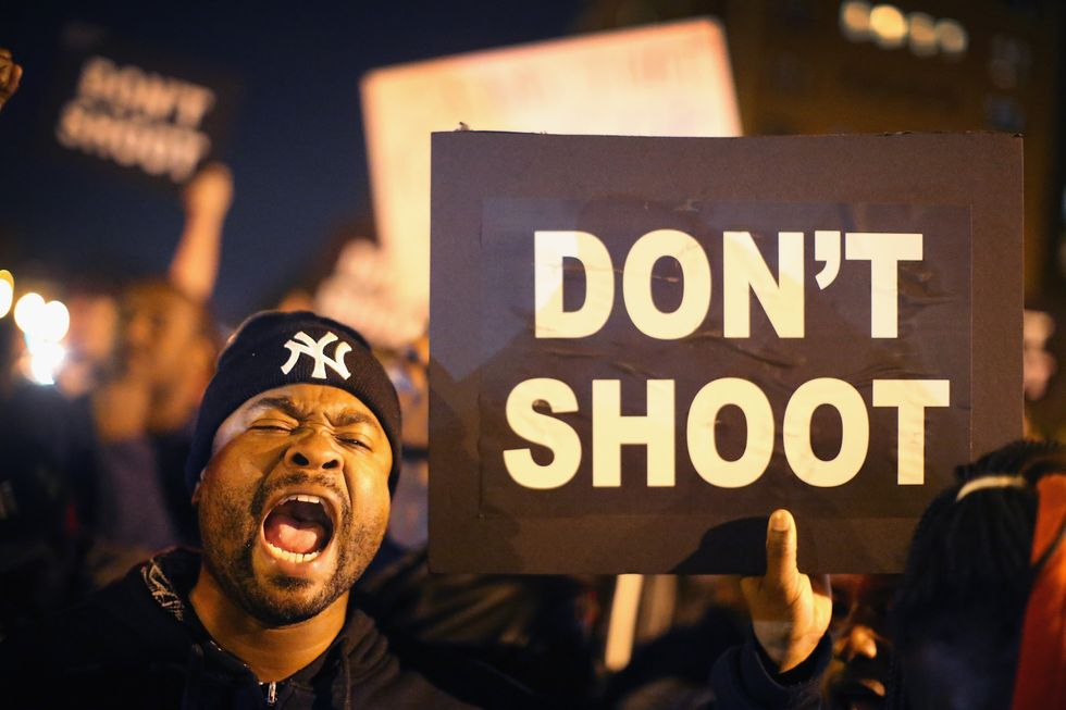 A Black Lives Matter protester holds a sign that reads 'Don't Shoot'
