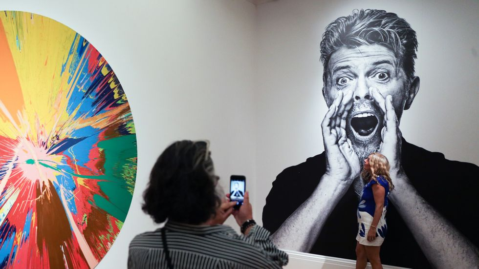 Visitors take a picture in front of a pictures of the British singer David Bowie and beside by one of the artworks (L) he owned named 'BEAUTIFUL, SHATTERING, SLASHING, VIOLENT, PINKY, HACKING, SPHINCTER PAINTING' by British artist Damien Hirst. (DANIEL LE