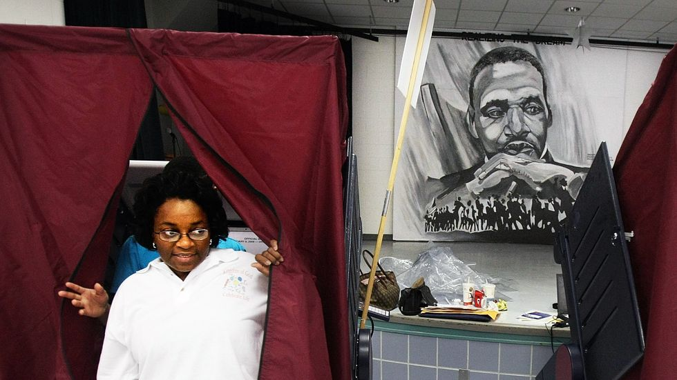 A woman exiting a Louisiana voting booth before an image of Dr. Martin Luther King, Jr.