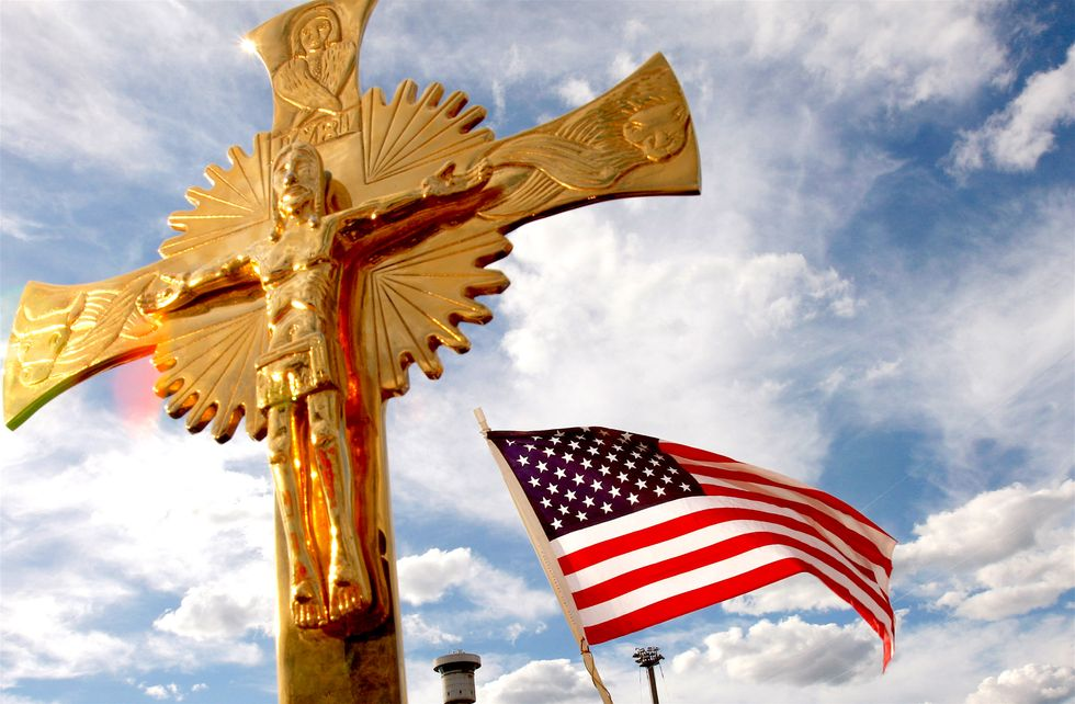A golden statue of Jesus on the Cross next to an American flag in the breeze.