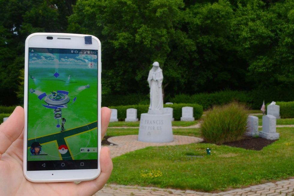Playing Pokemon Go in a local cemetery in Johnson City, NY. The statue of St. Francis in this memorial park has been deemed a Gym in the augmented reality game.