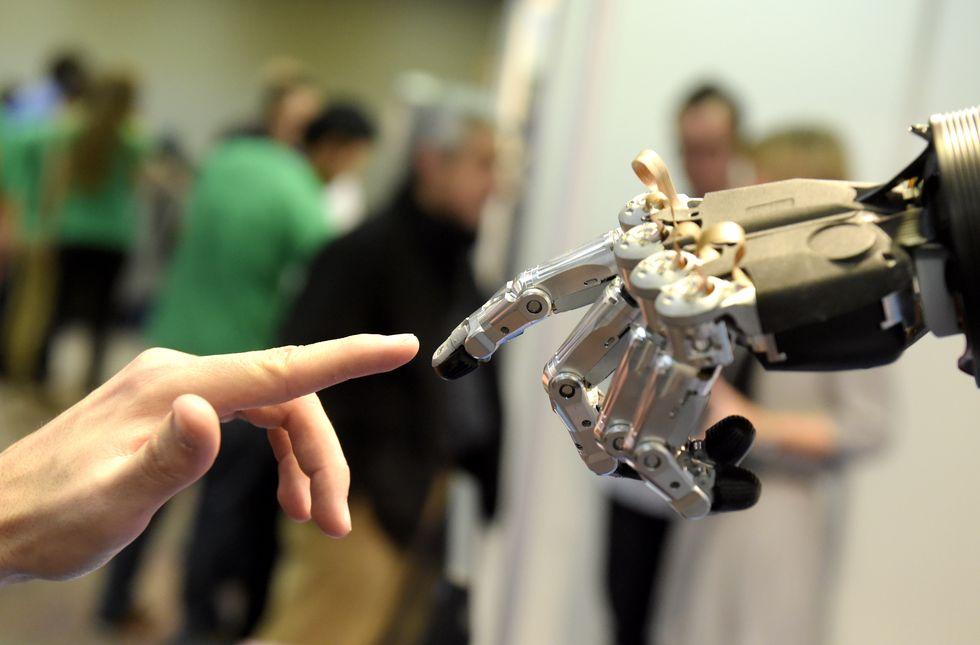 Robot and human hands touching.