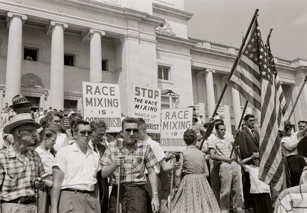 UNITED STATES - CIRCA 1959: people holding signs and American flags protesting the admission of the 'Little Rock Nine' to Central High School.