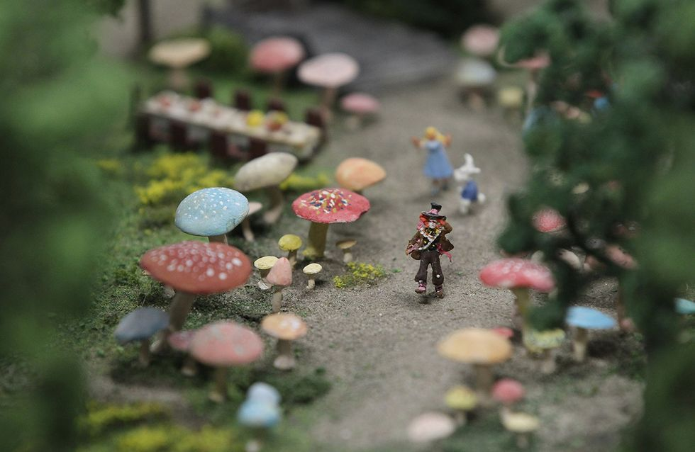 A miniature version of the Madhatter walks among rabbits and magic mushrooms from Alice in Wonderland.