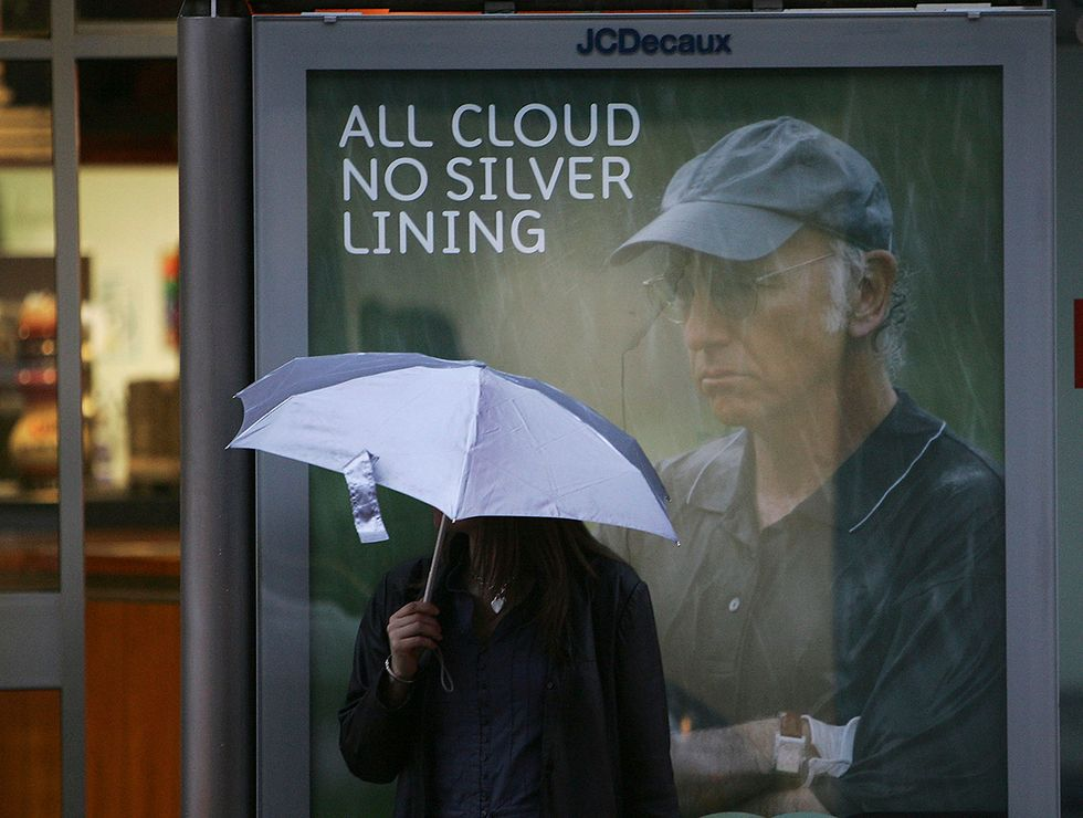 """GLASGOW, UNITED KINGDOM - OCTOBER 10: A woman waits for bus on her way home from work in Scotland. Behind her, a poster of Larry David with the words """"All cloud, no silver lining."""""""