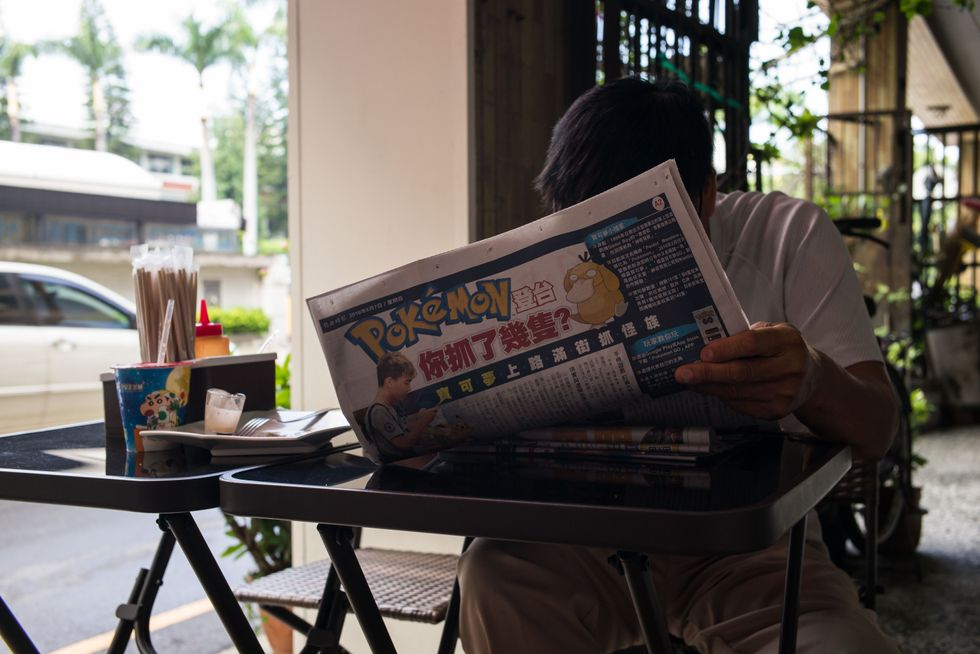 TAINAN, TAIWAN - AUGUST 08: A man reads a Pokemon Go article in the newspaper on August 7, 2016 in Tainan, Taiwan. 'Pokemon Go,' which has been a smash-hit across the globe was launched in Taiwan on 6th August. Since its global launch, the mobile game has