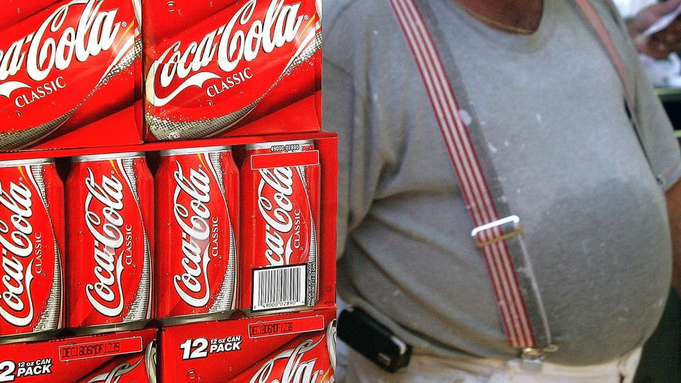 A heavyset man passes cartons of Coca-Cola displayed in a grocery store. (Tim Boyle/Getty Images)