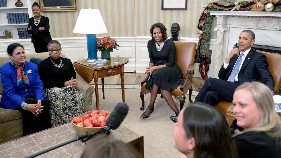 President Barack Obama and first lady Michelle Obama meet with mothers in the Oval Office. (Photo by Olivier Douliery/WHITE HOUSE POOL (ISP POOL IMAGES)/Corbis/VCG via Getty Images)