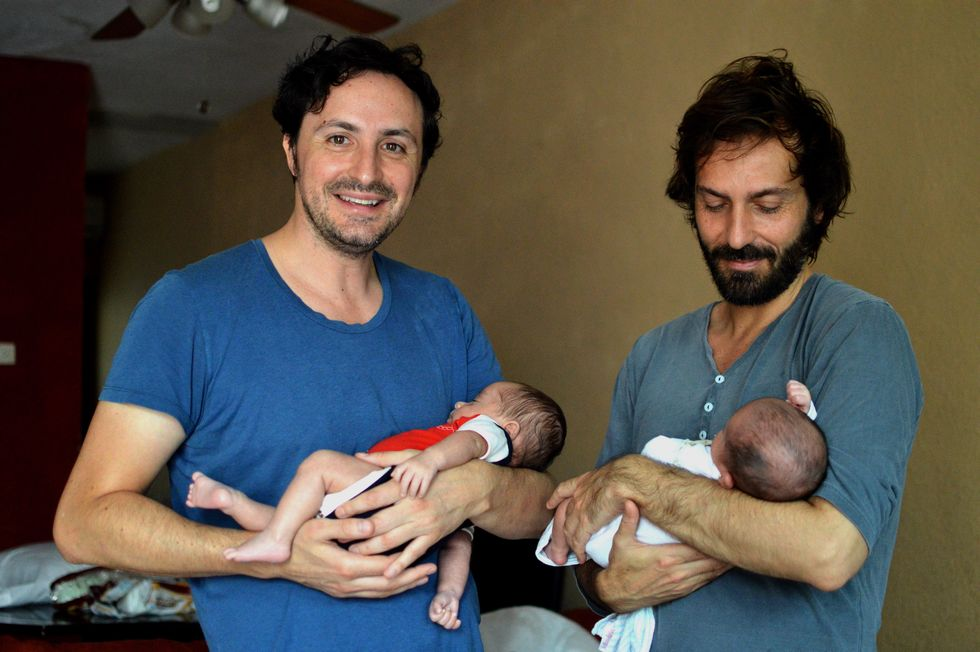 Two men each holding a baby.