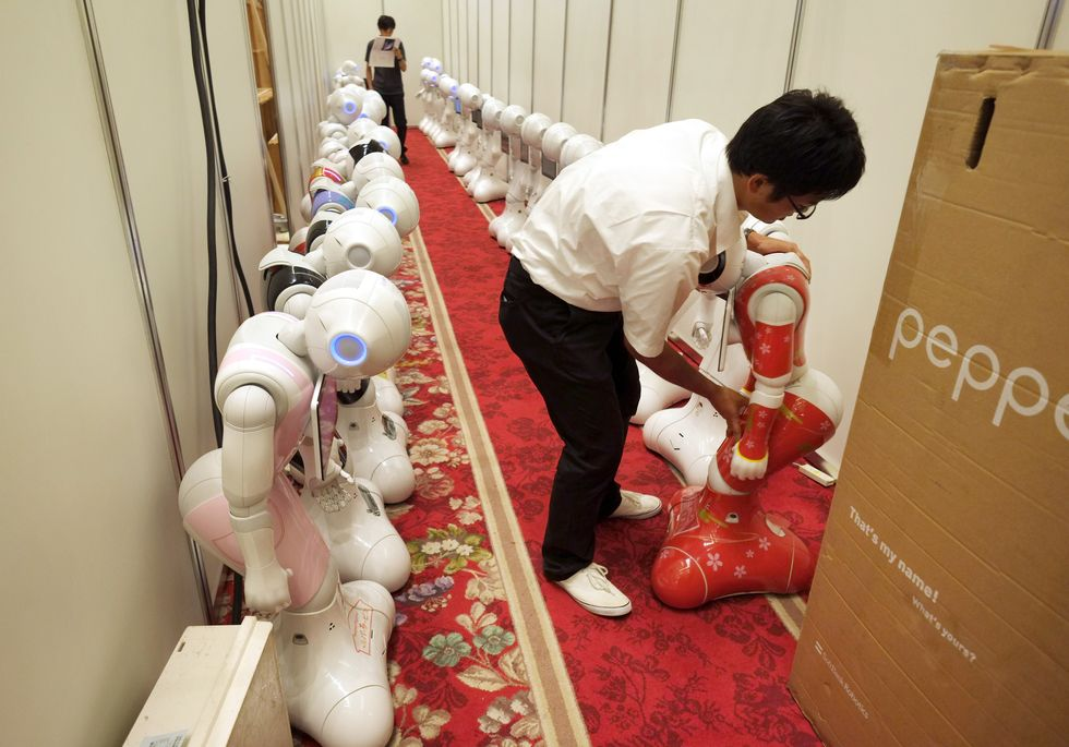 A worker arranges Japan's telecom giant Softbank's 'Pepper' humanoid robots in a hotel in Tokyo.