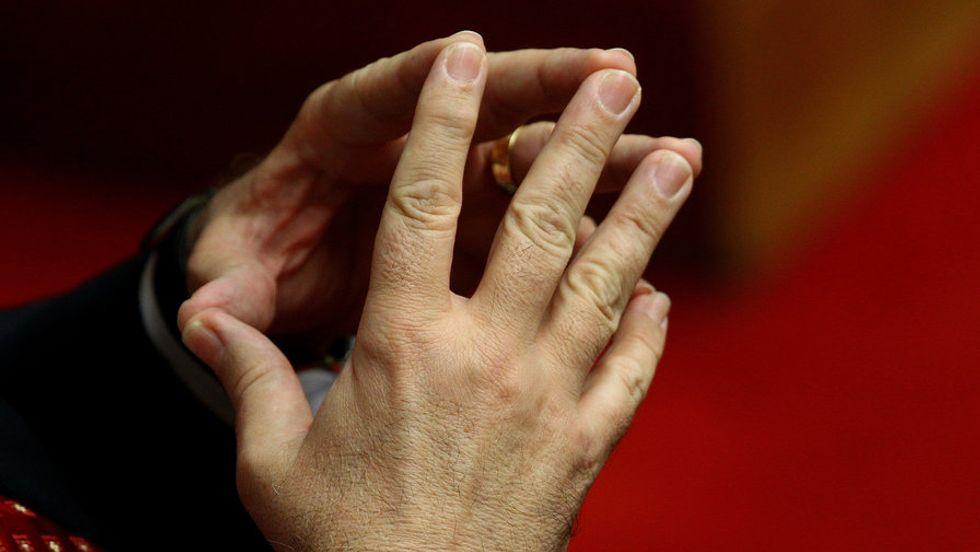 Hands pressed together at the fingertips.