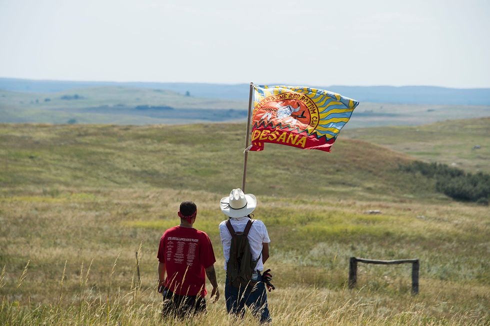 Native American protestors wave a clan flag over land designated for the Dakota Access Pipeline (DAPL), after protestors confronted contractors and private security guards working on the oil pipeline project, forcing them to retreat, September 3, 2016, ne