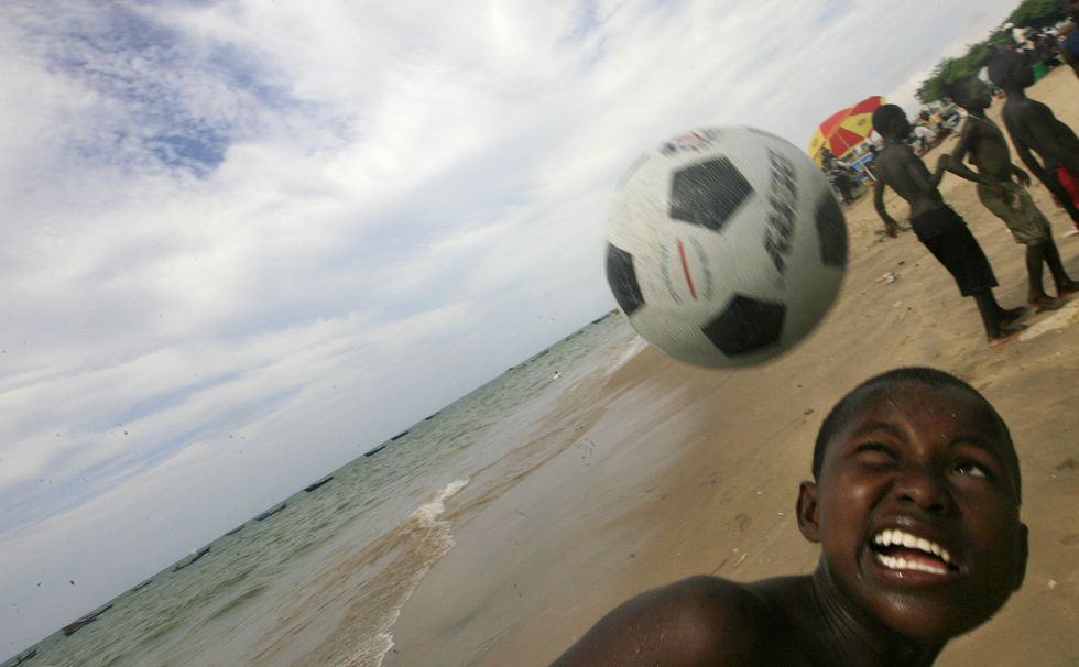 A young boy on the beach, about to head a soccer ball.