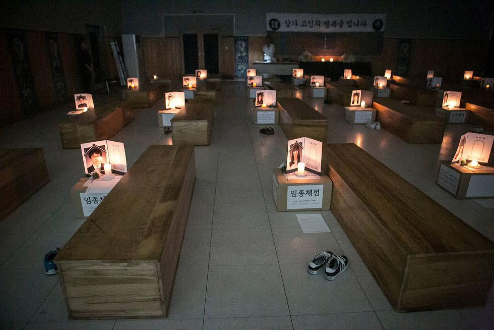 Participants think about their lives as they lie down in a coffin during a 'Death Experience/Fake Funeral' session held by Happy Dying on August 1, 2016 in Andong, South Korea. Fifty adults who work at the Andong Science College in South Korea participate