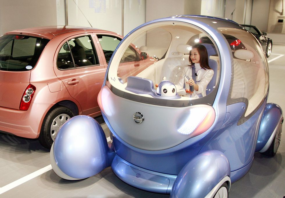 Japan's auto giant Nissan unveils the new robotic vehicle 'Pivo 2', equippeec with in-wheel electric motors to drive all wheels independently and to pivot its cabin at the company's headquarters in Tokyo. (Photo: YOSHIKAZU TSUNO/AFP/Getty Images)