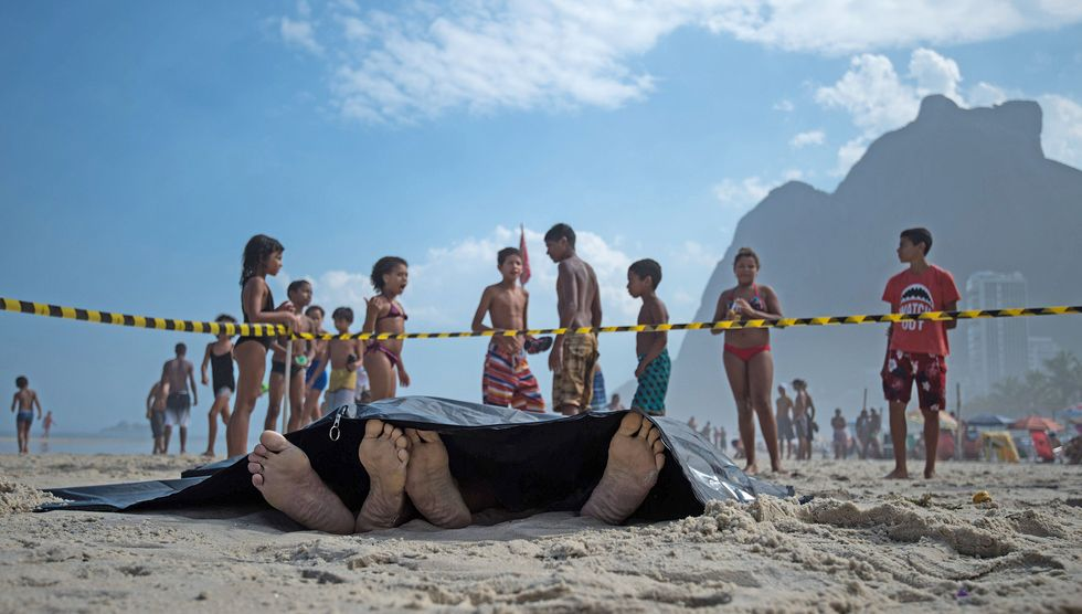 People remain at the beach near two corpses after the collapse of a bicycle track in Rio de Janeiro, Brazil. (Photo: CHRISTOPHE SIMON/AFP/Getty Images)