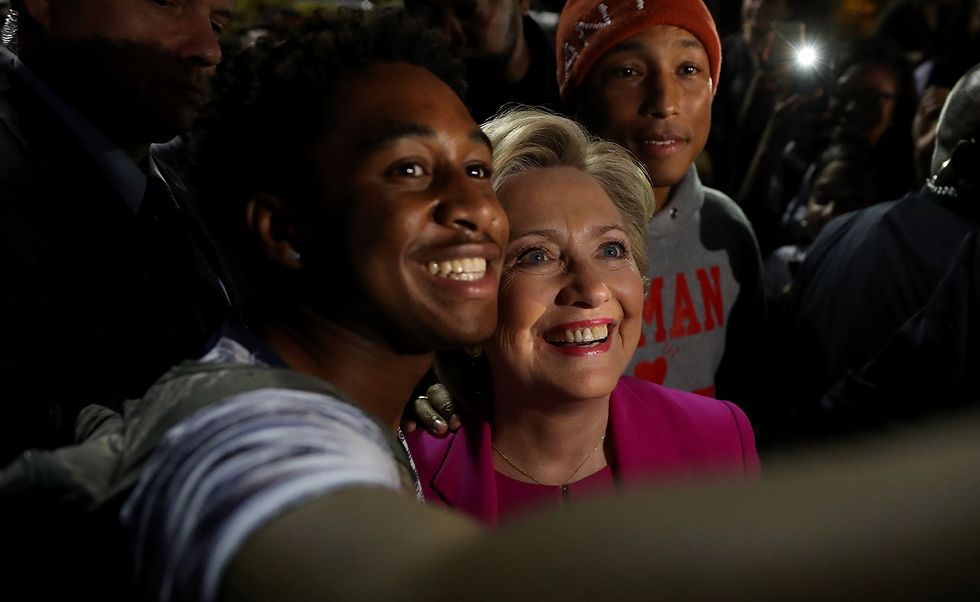 Democratic presidential nominee Hillary Clinton (C) and recording artist Pharrell Williams (R) take a selfie with a student at North Carolina Central University on November 3, 2016 in Durham, North Carolina. (Photo by Justin Sullivan/Getty Images)