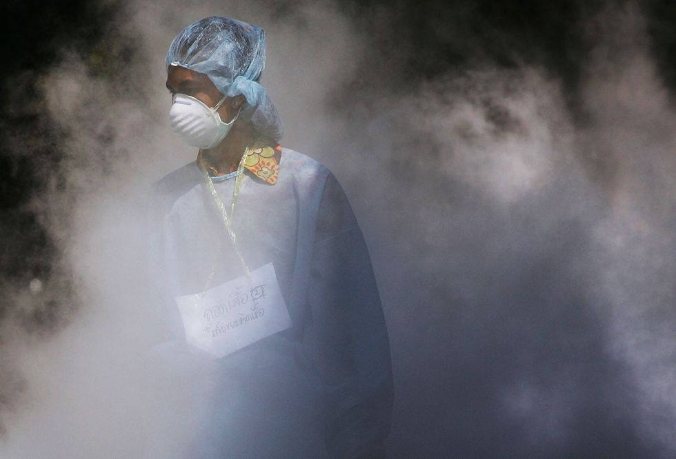 A medical professional walks through dry ice. (Photo by Chris McGrath/Getty Images)