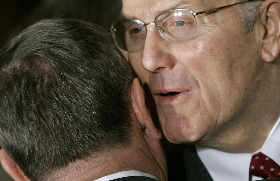 One man whispering into another man's ear. (Photo Paul J. Richards/AFP/Getty Images)