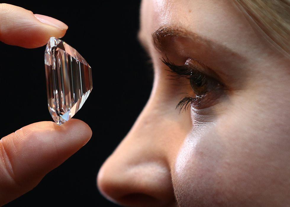 Woman examines a diamond.