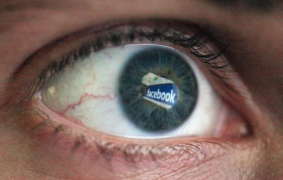 A person's eye with Facebook reflected in it.