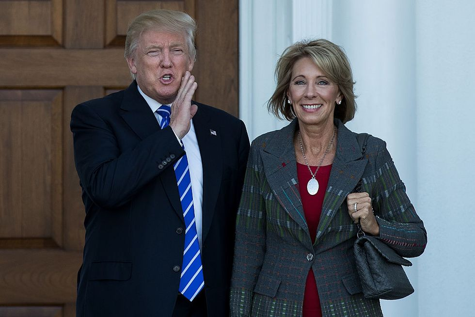 President Donald Trump and Betsy DeVos pose for a photo after their meeting at Trump International Golf Club, November 19, 2016 in Bedminster Township, New Jersey. (Photo by Drew Angerer/Getty Images)