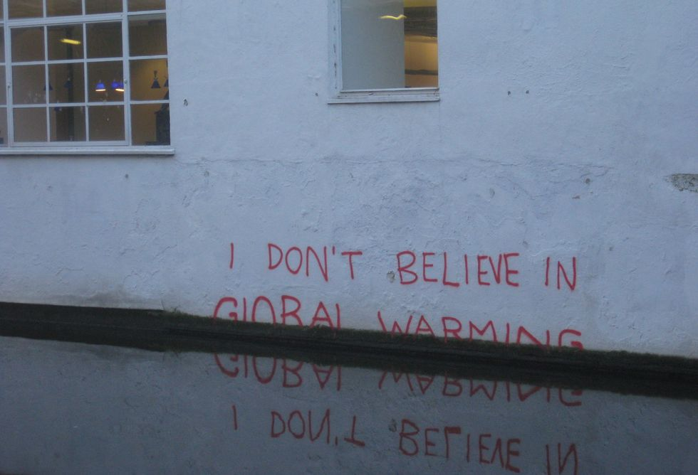 A half-submerged graffiti artwork on the wall of a river reads: 'I Don't Believe in Global Warming'