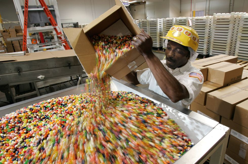 Kennie Bolden dumps jelly beans into a hooper that mixes the candy and gets it ready for packaging at the Jelly Belly candy factory