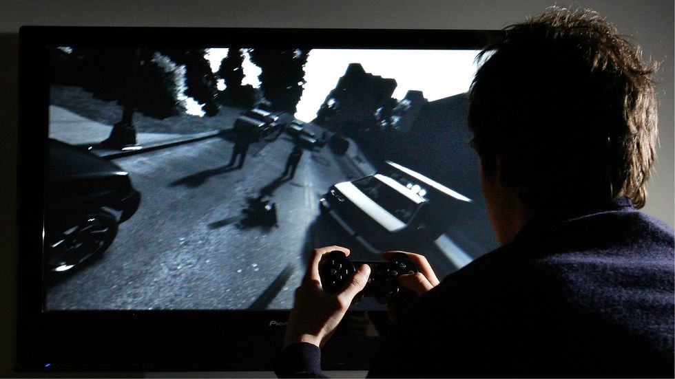 A young man plays Grand Theft Auto IV