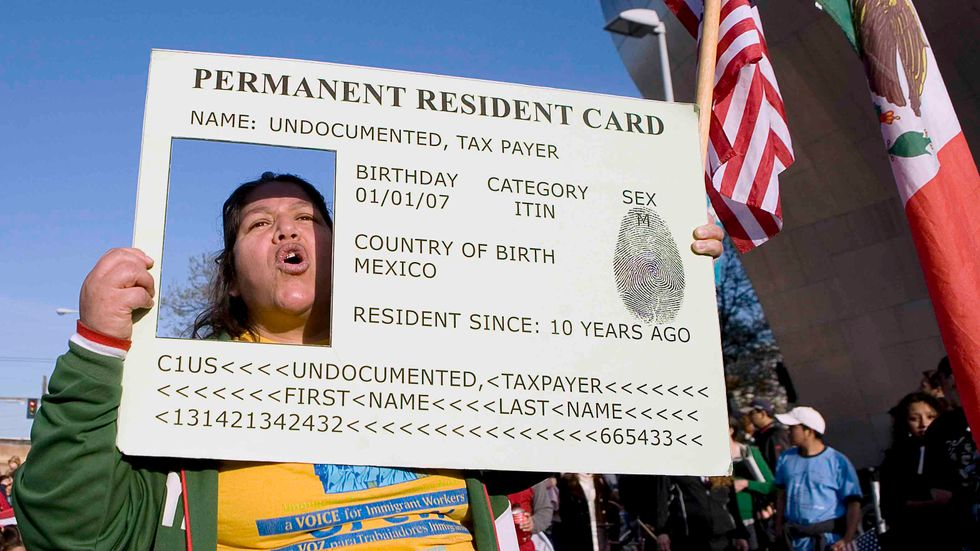 Josephine Corral of Tacoma, Washington, puts her head through a large green card replica during a May Day march May 1, 2008 in Seattle, Washington. (Credit: Stephen Brashear/Getty Images)