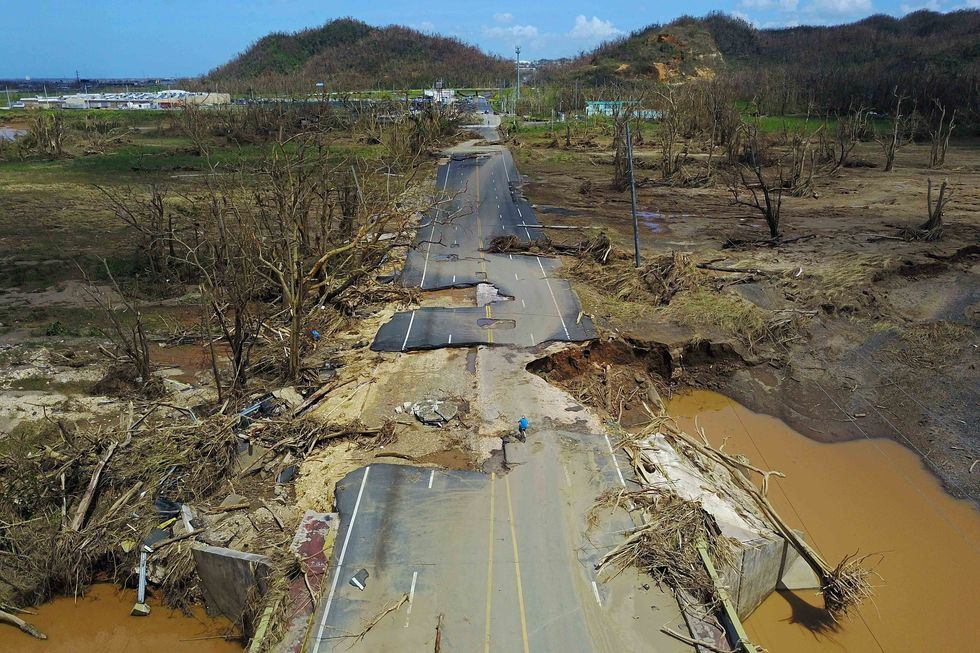 A man rides his bicycle through a damaged road in Toa Alta, west of San Juan, Puerto Rico, on September 24, 2017 following the passage of Hurricane Maria. RICARDO ARDUENGO/AFP/Getty Images)