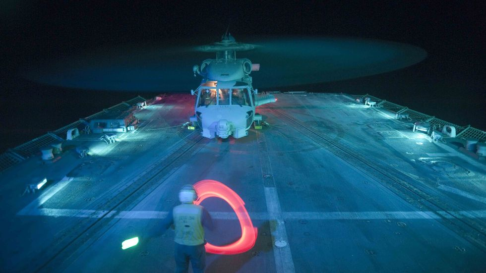A Sailor directs an SH-60B Sea Hawk helicopter as it prepares to shut down after landing aboard the guided-missile destroyer USS Nitze DDG 94, Gulf Of Aden, 2012. (Smith Collection/Gado/Getty Images)