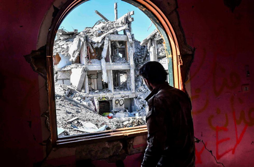 A member of the Syrian Democratic Forces (SDF), backed by US special forces, looks out from a building at the frontline in Raqa on October 16, 2017 in the Islamic State (IS) group jihadist' crumbling stronghold. (BULENT KILIC/AFP/Getty Images)