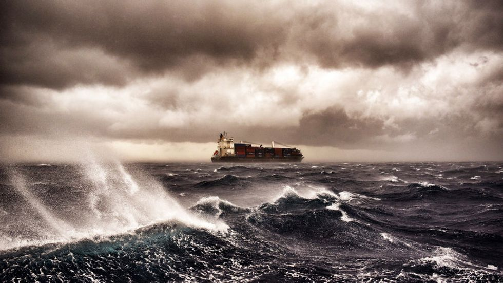 A cargo ship sails on the Mediterranean sea during a thunderstorm some 20 nautical miles from Malta on September 24, 2017. MESSINIS/AFP/Getty Images)