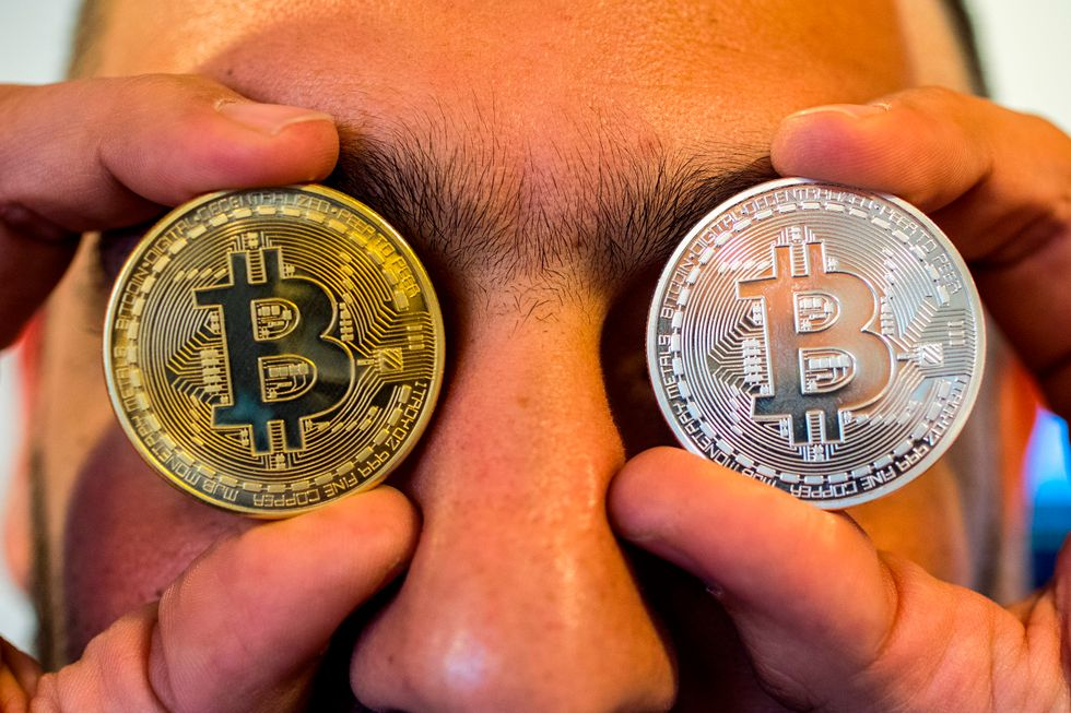 Man holding bitcoins over his eyes.