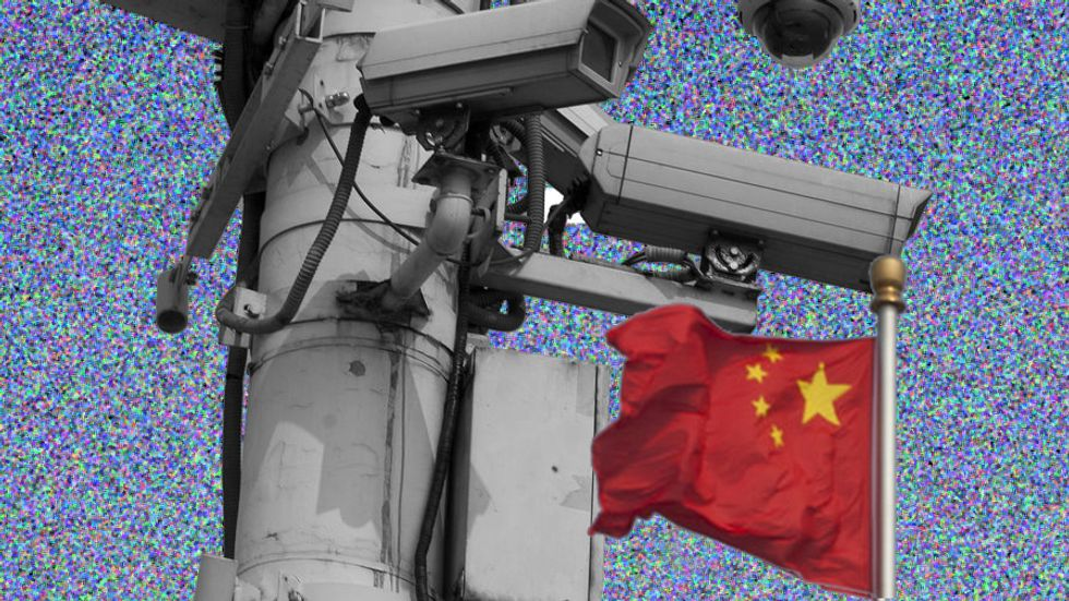 The Chinese national flag flies behind security cameras on Tiananmen Square. (Photo: Ed Jones/AFP/Getty Images)
