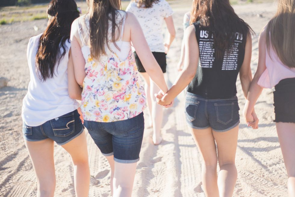 4 women holding hands and walking