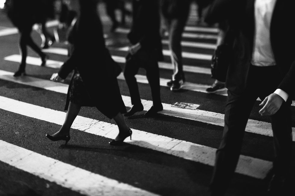 Black and white picture of people walking through a cross walk